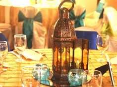 Touch of turquoise with the candle holders play nicely off the yellow tablecloth. Gorgeous for a reception or cocktail table.