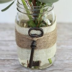 Embellish a mason jar with burlap, jute, and a faux vintage skeleton key to dress up a plain mason jar making it a rustic vase.