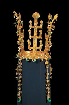 This crown is decorated with three oppositely-branched tree ornaments, and two antler-shaped ornaments placed on the band. The band is ornamented with two rows of dots made by pecking with a sharp-pointed tool such as an awl, a row of wave patterns, and a row of protruding dots between them. The entire crown is attached with many curved jades and golden spangles. Each of the tree-shaped standing ornaments has a trunk that is significantly larger than its opposing branches, revealing that…