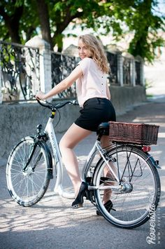 Blond european girl with curly hair on bicycle in a street. Fashionable cyclist, beige blouse with black collar and black shorts. Cycling in heels, fashion for cycling. Cycle chic photo #bicycles, #cycle chic, #fashion