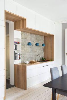 BENKEPLATE OVER, UNDER OG PÅ SIDEN: Arkitekt Torbjørn Tryti har kledd snittflatene med benkeplate i helstavs eik. De åpne hyllene rommer bøker på kjøkkensiden, og sko på baksiden.