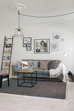 Nesta sala, a escada preta adiciona detalhe à decoração e serve de revisteiro e de suporte para a luminária