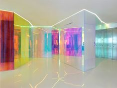 """Located on the Black Sea coast, Apartment """"H"""" by Re-Act Now, in Constanta, Romania, seeks to capture the seacoast feel with an open plan, predominantly white palette, and light flowing through ceiling to floor glass partitions laminated with 3M Radiant Color Film that continuously varies and shifts the hues with movement through the space."""