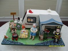 Caravan Camping in England - Caravan camping scene modelled for a Golden Wedding anniversary.  The raspberry ripple sponge Caravan cake was 16 egg mix.  The awning and all models are made from sugar and completely edible.  The whole set up was modelled from photos sent by the family so that everything was familiar to the happy couple with a few family jokes thrown in, hence the little girl dressed as a bumble bee for a fancy dress competition many years ago.