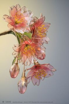 "These beautiful flowers may look like they are made of glass, but they are actually made from wire and liquid synthetic resin. Japanese Kanzashi (hair ornament) artist Sakae is the Maker behind this craft which she calls ""dip flower."" It involves bending a wire into a desired shape and then dipping it in a liquid plastic."