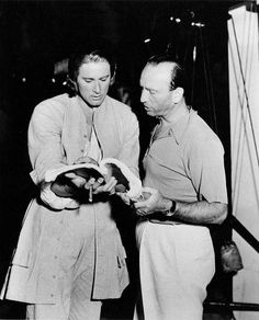 """Errol Flynn with director Michael Curtiz on the set of """"Captain Blood"""" [1935]."""