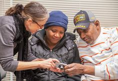 two women and a man viewing a digital image on a camera
