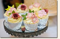 Exquisite cupcakes.  Silver liners; love the cream colored frosting with the flowers.  The mirror is a great reflection!!