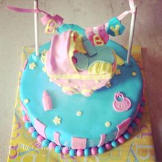 Baby Shower Cakes -  Blue and Pink Fondant Baby Shower Cakes with Pink Fondant Baby Crib and Hanging Baby Tags | All Things Yummy #allthingsyummy #babyshower #blue #pink #cakes #crib