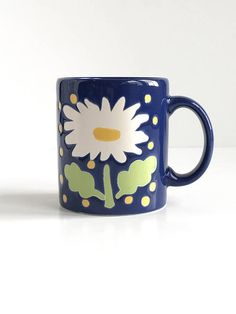 Hard to Find Waechtersbach Daisy Mug. A great gift for any Waechtersbach collector or someone who gardens and enjoys these lovely little flowers in the spring!  On a crisp blue background, with a white and yellow daisy and yellow polka dots around the middle. Its stamped Waechtersbach Spain on the bottom. This cup measures 3.75 T and 3.25D and holds 12 oz of liquid. Its in great vintage condition. There is are no chips, cracks or repairs to this mug.  We have some other great mugs listed…