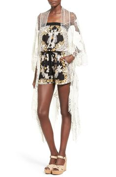 Add a statement-making layer to any warm-weather look with an airy lace kimono detailed with floral appliqués and long fringe trim.