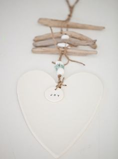 beautiful handmade white clay heart with a gloss glaze on one side, unglazed on other side allowing you to write a personalised message for a special occassion eg wedding, christening handmade pebble beads threaded onto natural twine with driftwood little 42mm clay disk with word 'joy' or 'love' tied with twine overall lenght can vary but approximately 600mm each caroline c piece is handmade so no two pieces are ever the same