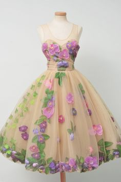 ecru tulle dress embellished with pastel flowers, ivy, and petals suspended in balloon skirt