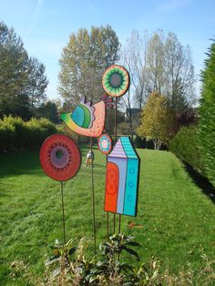 brightly colored wooden yard art pieces house bird circle flowers