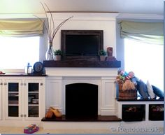Note the framed flat screen tv, mantle styled with wood beam look above wood mantle, wood hearth with top of solid material, window seat to the right under window. In case my home has a fireplace Backyard Fireplace, Fake Fireplace, Fireplace Mantle, Fireplace Design, Fireplace Ideas, Fireplace Seating, White Fireplace, Electric Fireplace, Cottage Fireplace