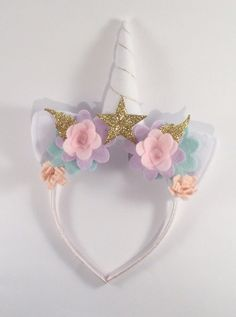Your child will want to wear this Woodland inspired unicorn headband everyday, it is so much fun! The ears and horn are handmade from white acrylic and the horn has polyester stuffing so it will stand up straight. The ears and horn are surrounded by enchanting pastel pink and lilac felt flowers with gold glittery leaves. The plastic headband is covered in pink satin ribbon making it very comfortable to wear.  Inspired by British fairy tales, the headband is a great accessory for a birthday…
