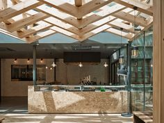 Kooo architects has added wooden beams to a cafe in China to form a woven lattice across the ceiling that lets in light