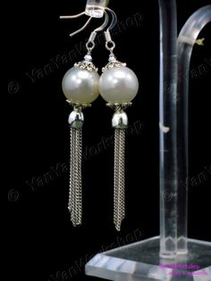 These elegant earrings feature a lustrous creme shell pearl with delicate silver finished metal chains tassel.