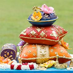 Pillow Talk An unlikely confluence of ideas—Indian pillows, tattoos and leis—inspired the unique design of this whimsical cake. Made for a yoga instructor's destination wedding, the sculpted pillows are adorned with jewels that resemble the rich fabrics and colors of Indian fabric. A custom swirl pattern on the bottom pillow takes a cue from the leis featured at the Hawaiian wedding, as well as the bride's white-ink tattoo. CakeLava, cakelava.com.