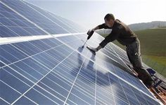 A worker mounts 320 square metres of solar panels on the roof of a farmstead barn in Binsham near Landshut March 21, 2012. REUTERS/Michaela Rehle/Files
