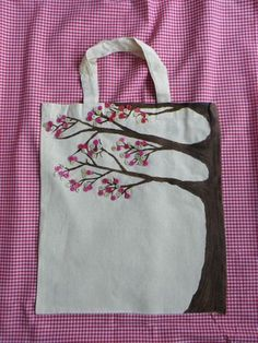 Natural 100% cotton canvas short handled bag with a unique hand painted tree design on front and decorated with buttons as the spring blossom.  Dimensions 37cmx42cm  Hand wash only in cool water.   This is an exclusive item designed by Hippychick Creations and is subject to copyright, please do not replicate this product.