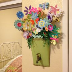 Handmade scrapbook paper flowers creatively arranged in a unique container with green crinkle paper fill to act as grass. FLOWERS THAT LAST FOREVER!