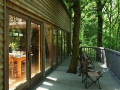Oak frame house in woods in Devon, UK Love the integration of the tree into the front, could this be inspiration for the house entrance with the existing tree?