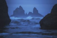 Coastal Castle - A blue morning along the scenic Oregon coast showcasing distant seastacks and crashing waves. The seastack in the back is covered with various birds and I liked how the edges of the two closer seastacks framed the jagged spires in the distance.
