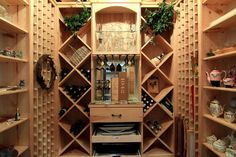 The WINE ROOM includes a fabulous brick floor, built-in wood wine storage/ shelving/cabinet space, hanging light fixture and glass door with decorative wrought iron accents.