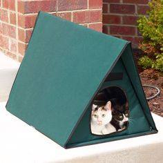 """The Only Multiple-Cat Outdoor Heated Shelter - his is the only outdoor cat shelter with a heated bed that keeps up to four felines warm and comfy in cool temperatures. The 1 1/2""""-tick soft foam bed has an integrated heater that generates radiant warmth that comforts outdoor cats. Its A-frame design, durable 600-denier nylon exterior with a waterproof vinyl backing, and roof overhang help keep felines dry during rain showers. Dual exits allow cats to come and go with ease and as they please."""