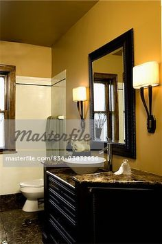 "Mediabakery - Photo by Sheltered Images - ""BATHROOM: Bright mustard colored walls, brown granite counters and floor, bowl sink, black mirror and vanity, white tile wall by window"" Black White Bathrooms, White Vanity Bathroom, Yellow Bathrooms, Brown Bathroom, Vintage Bathrooms, Bathroom Floor Tiles, Bathroom Wall, Wall Tile, Bathroom Interior"