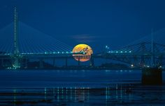 Harvest moon behind the Forth Bridges, including the almost complete Queensferry Crossing