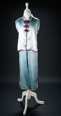 "Aqua-Blue Silk Satin Pajamas Worn by Shirley Temple in the 1936 Film ""Stowaway""Of softest aqua-blue silk satin, the two-piece set features a top with gently flared shaping, slightly dropped shoulders, and open front which fastens with soutache loops, trimmed with burgundy silk edging and soutache, and matching pants with snap closures at either side of the waist. Z"