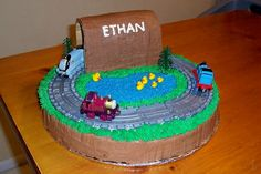 Thomas Cake 3 - 14 inch round single layer. Covered in buttercream frosting. Plastic track and trains. Water using blue sugar sprinkles. Ducks made of fondant. Covered bridge/tunnel out of cardboard and then covered with frosting... attached with toothpicks
