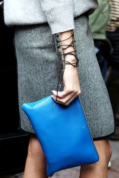 Grey cashmere sweater and pencil skirt with a bright blue clutch bag