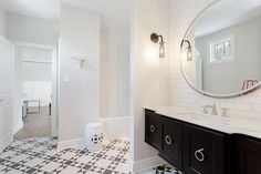 Stunning black and white bathroom features a black floating washstand fitted with large nickel ring pulls and a marble countertop holding a sink with a polished nickel faucet kit positioned beneath a large round vanity mirror mounted on a white linear tile backsplash and lit by bronze and glass globe wall sconces. Ring pulls