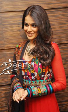 Genelia D'Souza at Naa Ishtam Audio Success Meet. Wearing a traditional Sindhi Embroidery Anarkali Frock in red paired with a black plain churidar and embroidered shawl. This Anarkali Churidar is heavily embroidered all over the hem and laced up in red and sea green, the small mirror work is beautifully enhancing the colorful hand embroidery, …