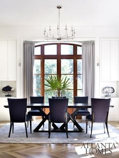 Elegant dining space with a chandelier, gray curtains, and dark violet chairs