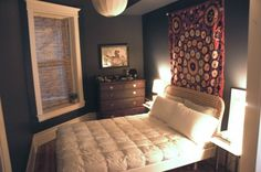 You can paint small rooms dark colors. I would probably go with grey rather than black.  Like the simple colors with bright, elaborate tapestry.  Also like light and window shade