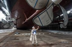 Ship's sponsor Susan Ford Bales, President Ford's daughter, touches one of the giant propellers during a tour of the ship before the dry dock flooding. Photo by Chris Oxley