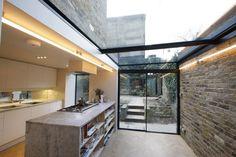 extension de maison avec îlot central en marbre gris, meubles de cuisine blanc neige et sol en parquet chevron
