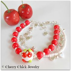 A sweet Cherry bracelet designed with tomato red glass beads, silver heart chain, and a whimsical lampwork glass cherry bead. #Cherries #CherryBracelet #CherryJewelry #BeadedBracelet