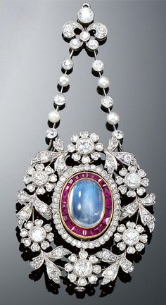 MOONSTONE, RUBY, PEARL AND DIAMOND BROOCH/PENDANT, CIRCA 1900. Designed to the centre as an oval cluster centring on a cabochon moonstone within surrounds of calibré-cut rubies and scalloped millegrain-set single-cut diamonds, within a frame in the garland style composed of flower heads and foliage set with single- and circular-cut diamonds, suspended from two rows of alternating seed pearls and collet-set circular-cut diamonds, to a similarly-set stylised foliate surmount, fitted case.