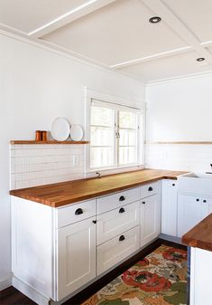 love. subway tile. butcher block countertops. white square-paneled cabinetry. plate rail. no upper cabinets. dark hardware. farm sink. overscale floral rug. love everything about it.