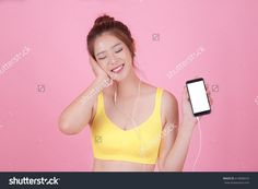 Beautiful young woman in headphones listening to music smiling with closed eyes standing on a pink background and blank mobile phone.