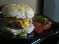 Triple Cheese Burger. Homemade burger made with ground beef and soy sauce to bind the beef into burgers. Edam cheese was placed inside the burger and a cheese slice with salad was on the burger. The bun was baked with chedder cheese on top.