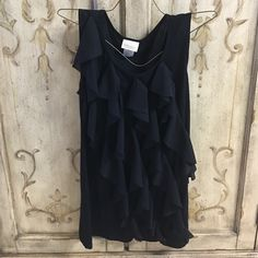 Boutique Top Very cute sleeveless top rayon/spandex blend. Has semi sheer ruffles going down front which makes like a cap sleeve look on one side. Pretty Good Tops