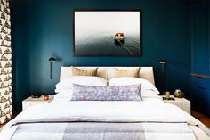 Moody bedroom with dark blue walls bronze sconces, and photography