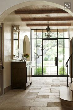Steel door, bleached wood ceiling, limestone floor, plaster walls, arched doorways -- love the floors spilling through the foyer past the stairs Steel Windows, Steel Doors, Windows And Doors, Halls, Bleached Wood, Limestone Flooring, Travertine Pavers, Entry Hallway, Entrance Hall