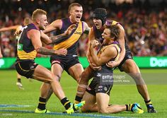 Sam Lloyd of the Tigers is congratulated by Dustin Martin, Ben Griffiths and Brandon Ellis of the Tigers after kicking the match-winning goal after the final siren during the round eight AFL match between the Richmond Tigers and the Sydney Swans at the Melbourne Cricket Ground on May 14, 2016 in Melbourne, Australia.
